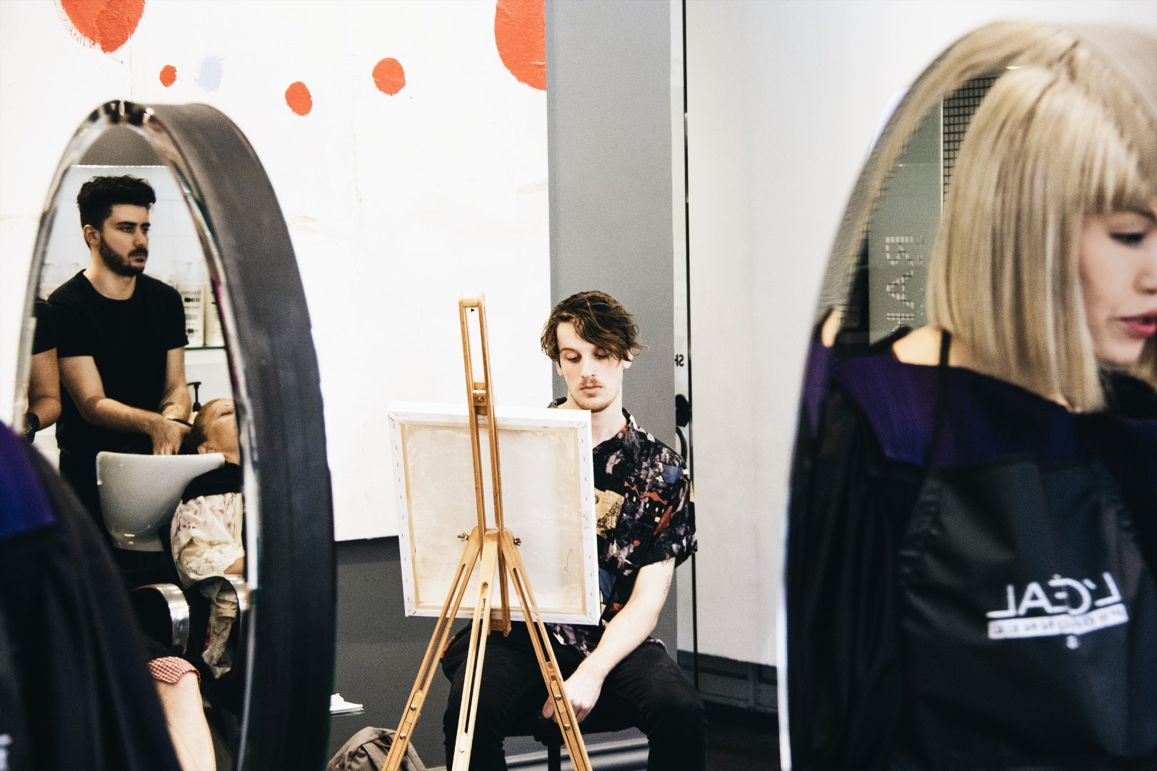 An artistic shot of artist Brendan Hartnett at work, with Style Director Pasquale and Stylist Hanae reflected